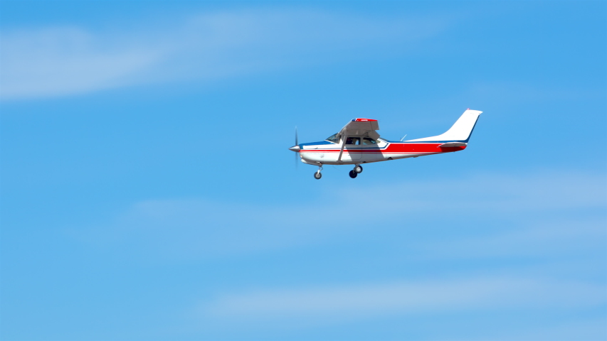 Generic Small Private Single Engine Airplane Flying in a Sunny Blue Sky with Thin White Clouds
