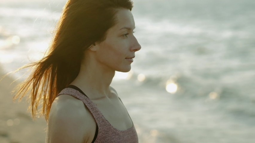 Young beautiful woman in sportswear standing on a sandy beach and looking at the Mediterranean sea in the morning. Spain. Slow motion. HD   Shutterstock HD Video #1040861306