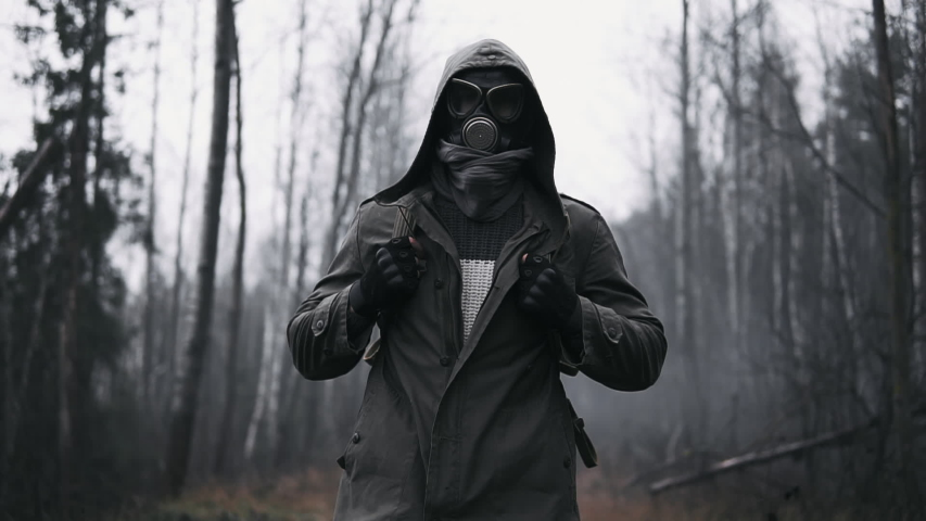 Wandering man in military clothes and gas mask walking on old rail in empty dark forest. Stalker concept, survivor after nuclear or chemical war. Post apocalyptic world. Stedicam following shot | Shutterstock HD Video #1040861837