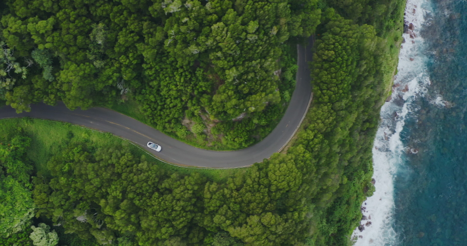 HAWAII, USA - CIRCA NOVEMBER 2019: Tesla Model 3 in the wild: Aerial view of a white luxury car driving on a windy coastal green jungle road with blue ocean, island vacation adventure