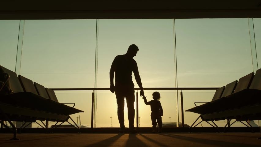 Silhouette of father and his little kid waiting for departure walking around in airport lounge room together before vacation - family, adventure concept 4k footage | Shutterstock HD Video #1040889551