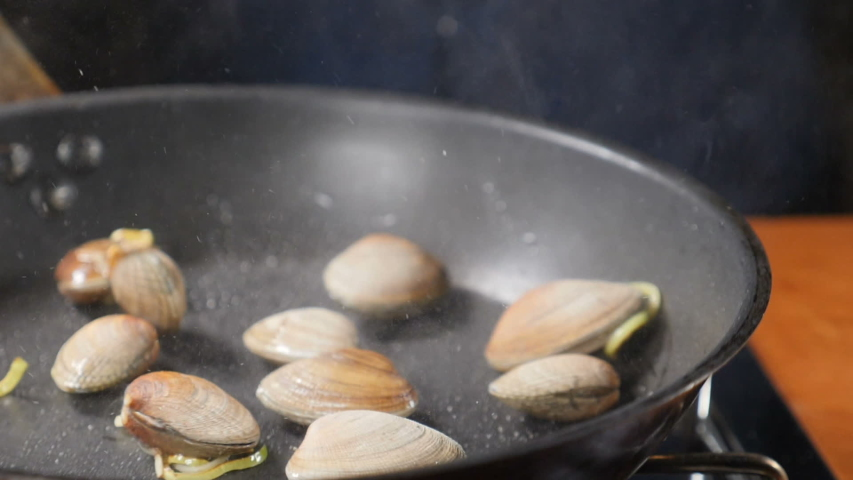 Closeup shot of chef hands cooking mussels in shells tossing, mixing and throwing on pan., seafood being cooked in frying pan at restaurant kitchen, Pasta with seafood. Slow motion. Shot in hd