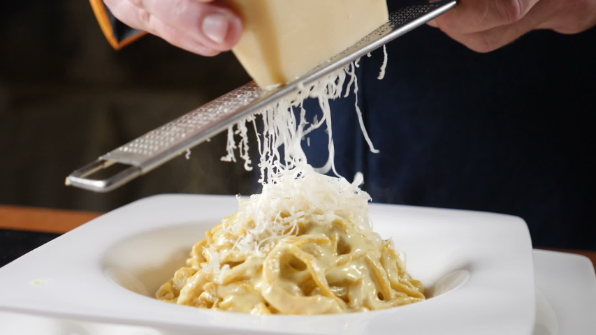Foodvideo footage shot in slow motion. Cheese is being grated on the plate of freshly-cooked Italian pasta. Chef grating hard cheese. Cooking seafood pasta. Shot in hd