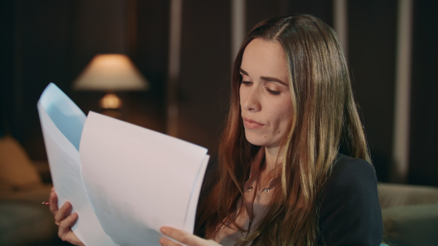 Focused woman reading financial report in office at evening. Portrait of pensive businesswoman looking documents in hotel. Close up of thoughtful business woman working with papers at home | Shutterstock HD Video #1040895041