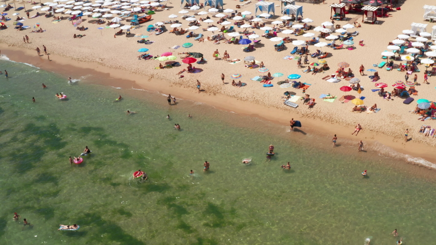 Aerial view sea coast tourist drone flying up of sandy beach. View of the beautiful beaches colorful umbrellas beaches. Resort. Summer holidays, tourism. Shkorpilovtsi, Bulgaria. Top view. Copy space