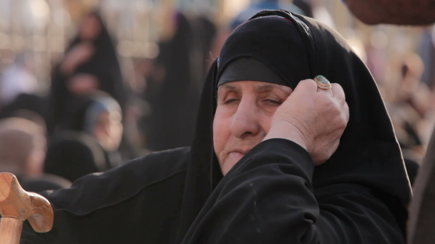 HUSSEIN'S SHRINE, KARBALA, IRAQ - 2017: A very old woman visiting Imam Hussein's shrine. Every year, millions of Shiite Muslims come from all over the world to Karbala to visit Imam Hussein's shrine.