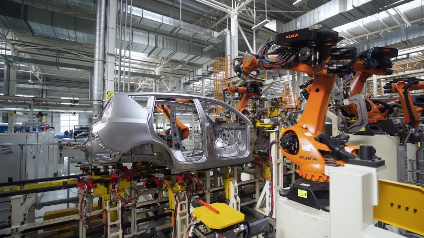 BELARUS, BORISOV - AUGUST 7, 2019: Automobile plant, modern production of cars, car body welding process, robots at work, build process in automated production line.