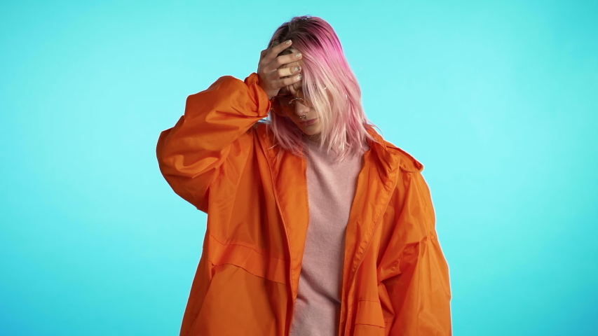 Frustrated unusual woman with pink hair over blue wall background. Girl is tired of work or studying, she disappointed, helpless | Shutterstock HD Video #1040907149