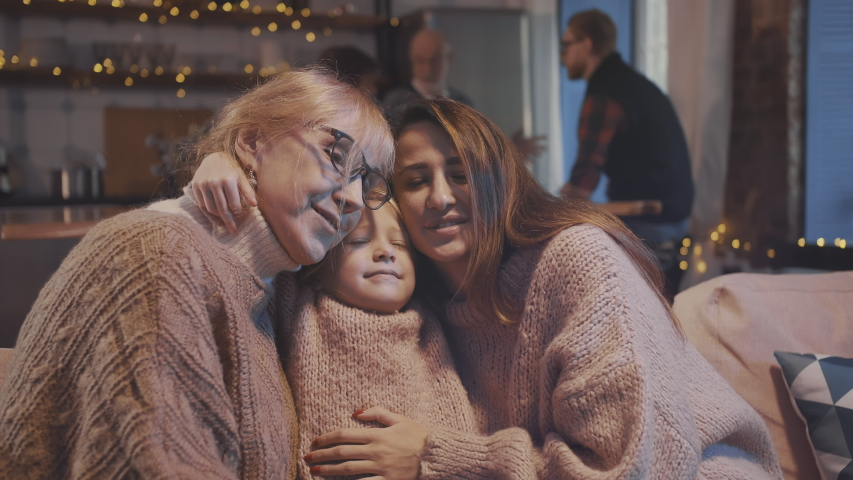 Portrait of three multi-aged beautiful women hugging and kissing on couch. Large family gathering together to celebrate christmas in modern decorated apartment.