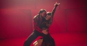 Beautiful couple dancing latin dance . Professional dancers dancing flamenco , rumba or salsa on red background . Pair in spanish dress performs dance movement . Shot ARRI ALEXA Cinema Camera .