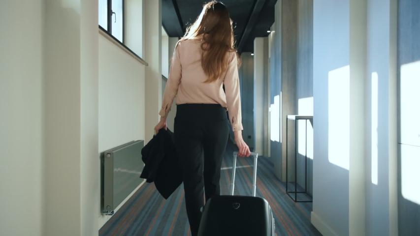 Businesswoman with travel suitcase walking at hotel corridor. Traveling woman with baggage settling in business hotel. Woman arriving in hotel for business trip