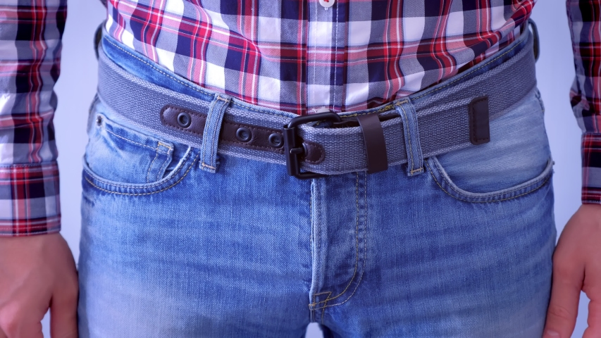 Man in jeans with modern belt and plaid shirt, waist closeup. Casual style. He is wearing jeans and plaid shirt, waist closeup. | Shutterstock HD Video #1040926535