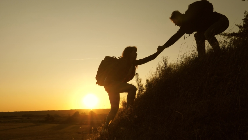 Tourists climb the mountain at sunset, holding hands. teamwork of business people. Traveler man holds out woman's hand to a traveler climbing to the top of the hill. Happy family on vacation. | Shutterstock HD Video #1040943776