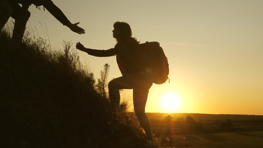 Tourists climb the mountain at sunset, holding hands. teamwork of business people. Traveler man holds out woman's hand to a traveler climbing to the top of the hill. Happy family on vacation. #1040943785