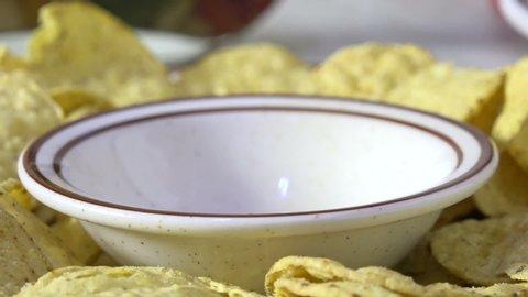 Pouring gourmet salsa into a bowl close up