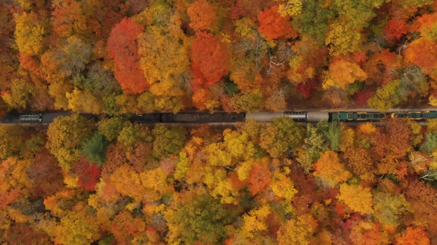 Aerial view of a vintage passenger train traveling through autumn foliage in the New Hampshire mountains