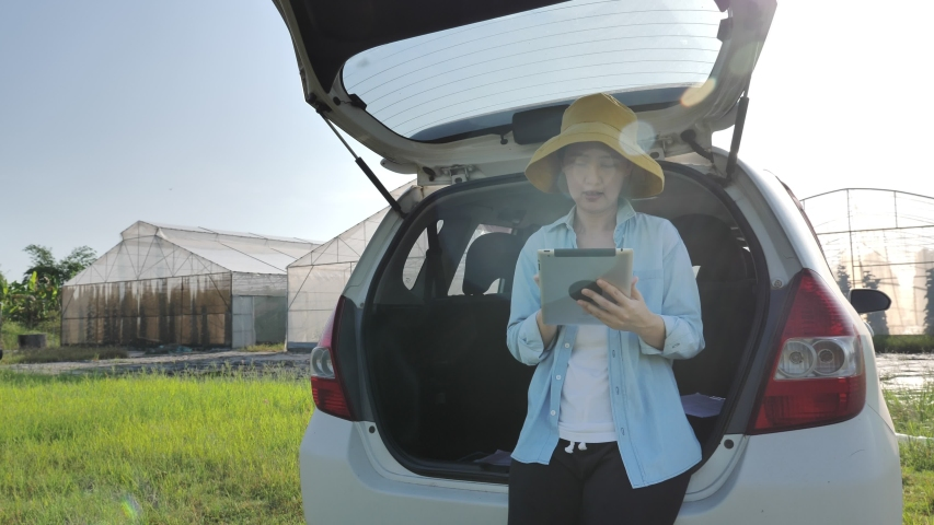 Smart Asian woman farmer sitting on car and using digital tablet for internet access front of green house, Smart agriculture concept