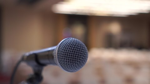Microphone in meeting conference hall for speaker at podium presentation, abstract blurred of speech in communication, speaking room with audience chairs, Talk business of event background.