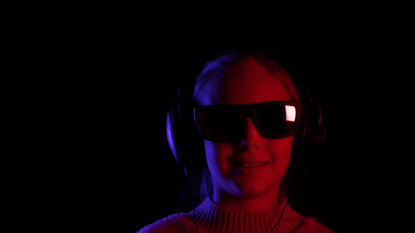 Girl in sunglasses and headphones browsing phone in darkness. Portrait of cute teenage girl in dark glasses using smartphone and listening music in headphones on black background #1040996405