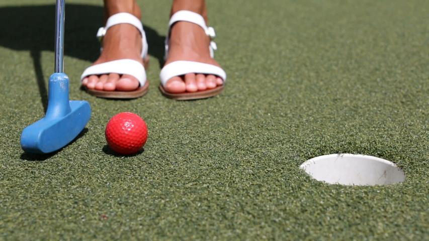 Mini golf or Miniature golf, putt-putt. - woman putting with golf club ball in hole.