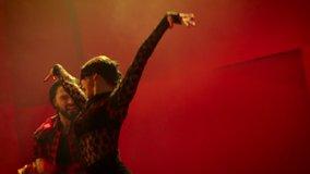 Beautiful couple dancing latin dance . Professional dancers dancing flamenco , rumba or salsa on red background . Pair in spanish dress performs dance movement . Shot on ARRI ALEXA Cinema Camera .
