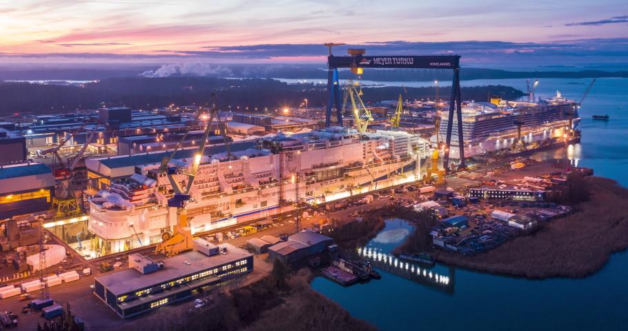 Turku, Finland - November/2019: Aerial timelapse of cranes, machines and people building a huge cruise ship in Meyer Turku Shipyard. DCI 4K shipbuilding time lapse.