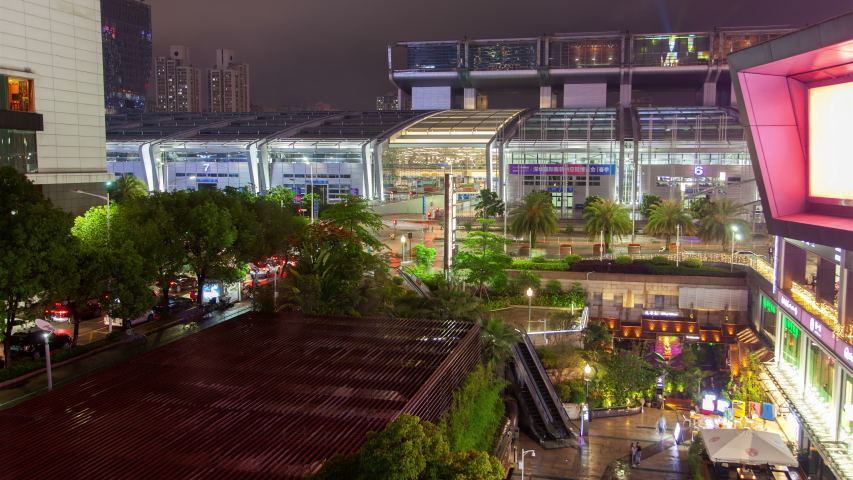 SHENZHEN/CHINA - JULY 07 2019: Timelapse famous Shenzhen Convention Exhibition Center transparent wall windows with coloured illumination and green trees at night | Shutterstock HD Video #1041034055
