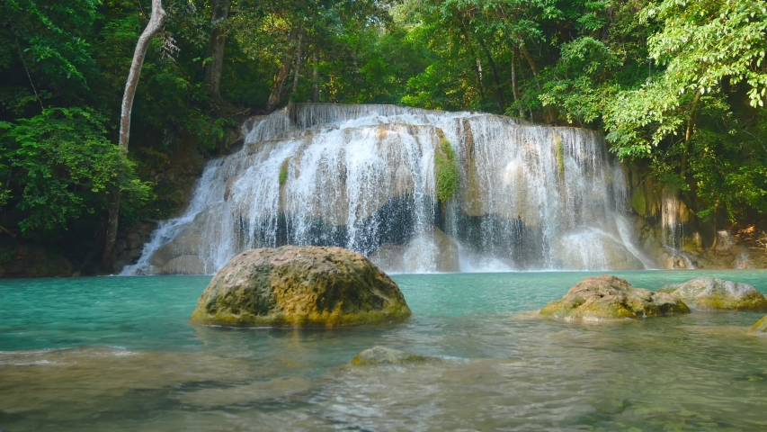 Natural scenery of beautiful Erawan waterfalls in a tropical rainforest environment and clear emerald water. Amazing nature for adventurers Erawan National Park, Thailand | Shutterstock HD Video #1041037634