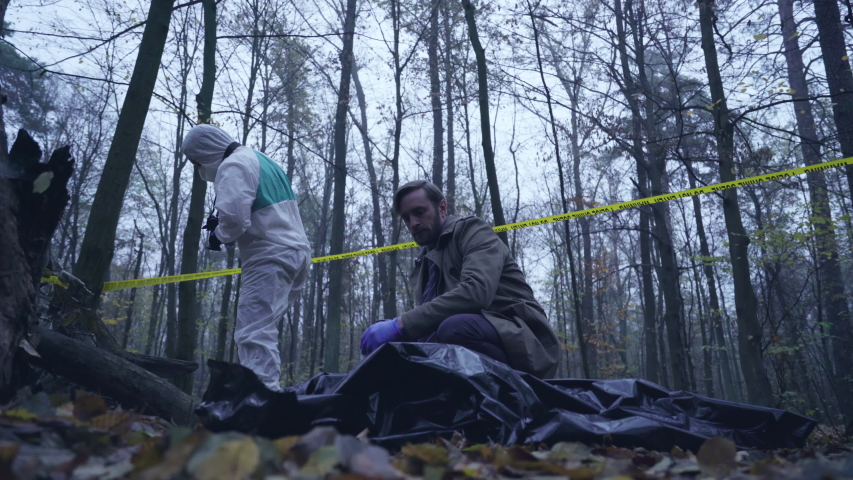 Detective looking at maniac victim body, forensic experts examining crime scene