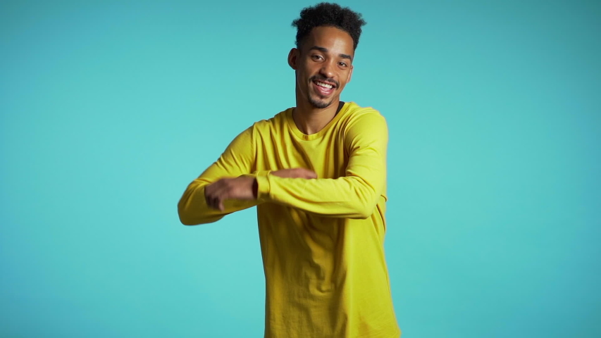 Young african american man smiling and dancing challenge dance in good mood on blue background.Unstoppable fun, happiness, comical portrait of guy isolated.