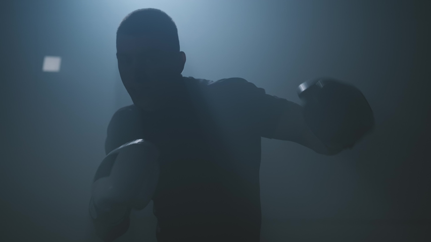 Male boxer punching to camera. Silhouette of young boxer practicing boxing punches looking at camera in dark smoky gym. Close-up in 4K, UHD