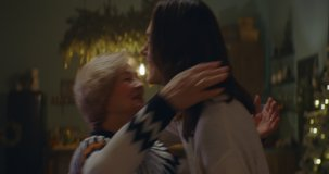 Adult daughter giving elderly mother a hug as multi generation family celebrate Christmas at parents home. Shot on ARRI Alexa Mini with Cooke 2x Anamorphic lenses. 4K UHD RAW Graded footage