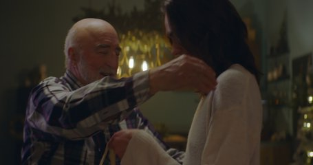 Adult daughter giving elderly father a hug as multi generation family celebrate Christmas at parents home. Shot on ARRI Alexa Mini with Cooke 2x Anamorphic lenses. 4K UHD RAW Graded footage