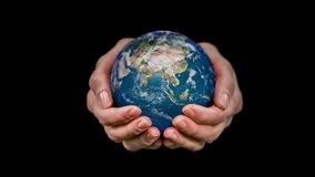 Female hands holding a rotating hyperrealistic Earth over black background.