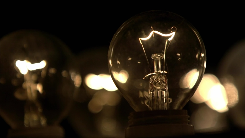 The incandescent lamp with a tungsten filament wobbles on the wire. The light flashes . Light from a light bulb. Bulb close-up. | Shutterstock HD Video #1041061052