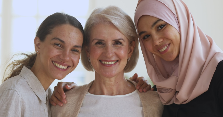 Three diverse smiling young and old women friends colleagues embracing looking at camera, happy beautiful different generations asian muslim and caucasian ladies bonding together, close up portrait