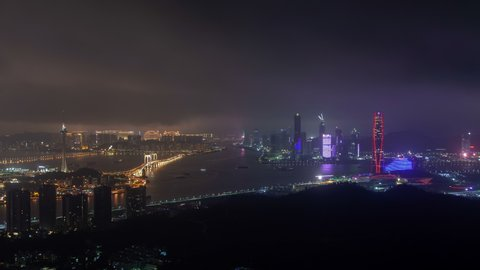 Timelapse large river border between Macao and Zhuhai cities with bright illumination on towers bridges and skyscrapers at night in China