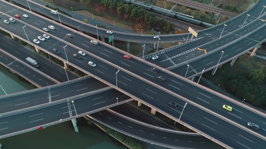Aerial view of road junction with moving cars. Road interchange or highway intersection with busy urban traffic speeding on the road. | Shutterstock HD Video #1041069401