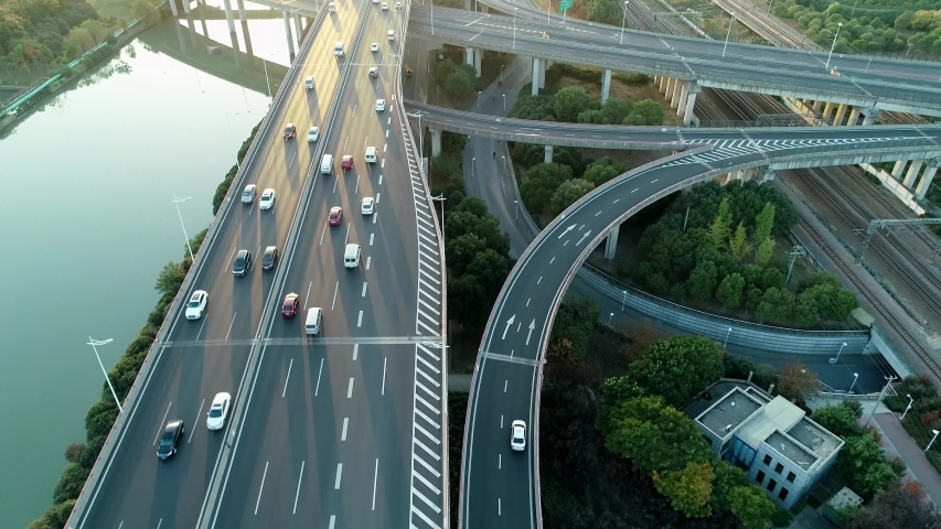 Aerial view of road junction with moving cars. Road interchange or highway intersection with busy urban traffic speeding on the road. Royalty-Free Stock Footage #1041069410