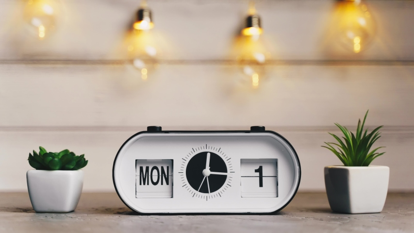 A white flip clock on table turns through month, flipping days and date, countdown from 1st to 31th