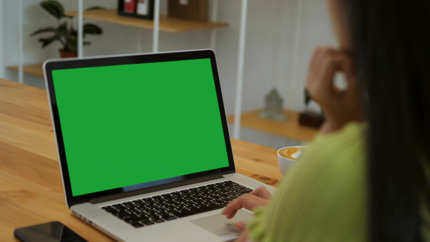 Over the shoulder shot of a business woman working in office interior on pc on desk, looking at green screen. Office person using laptop computer with laptop green screen, sitting at wooden table | Shutterstock HD Video #1041073427