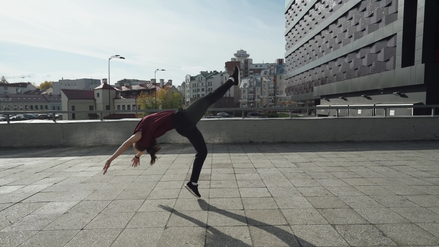 Young female gymnast runs in the city and doing a series of flips on training area near modern buildings.