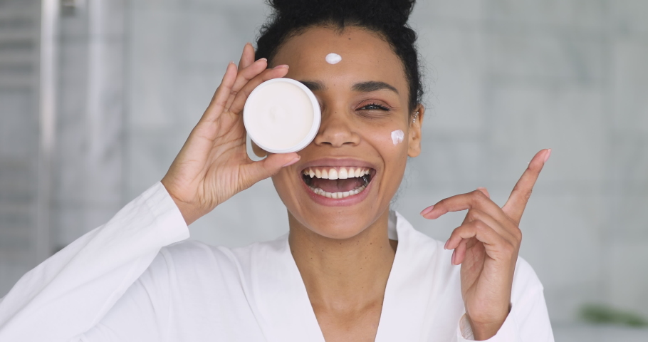 Happy beautiful african young woman apply cream on face laugh looking at camera holding creme jar in bathroom pointing aside advertise facial skin care moisture treatment hydration, skincare concept