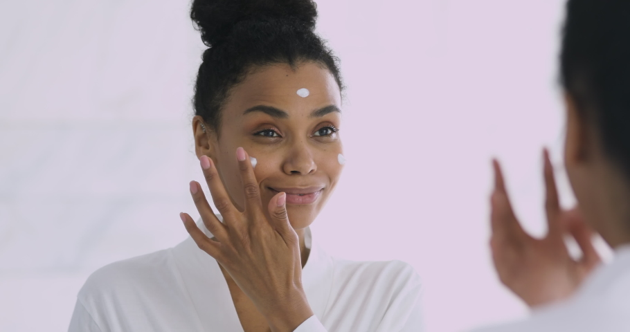 Happy confident attractive young african woman applying cream on face doing morning spa make up routine in bathroom look in mirror enjoy healthy clean soft moisturized hydrated skin, skincare concept