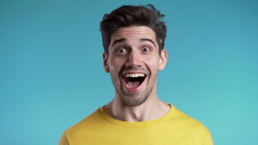 Amazed european man shocked, saying WOW. Handsome guy with stylish hairdo surprised to camera over blue background. Royalty-Free Stock Footage #1041091162