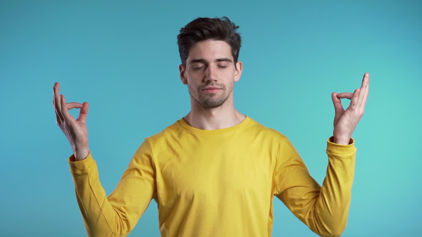 Calm student guy or businessman relaxing, meditating. Handsome european man calms down, breathes deeply with mudra om. Slow motion. Studio footage. | Shutterstock HD Video #1041091189