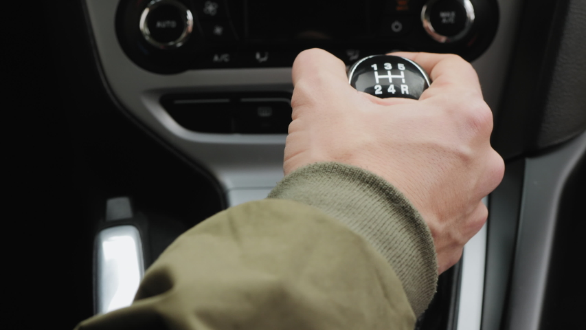 Driver man controls auto and switch gears, then shifts to neutral gear and pulls the handbrake handle, close-up shot