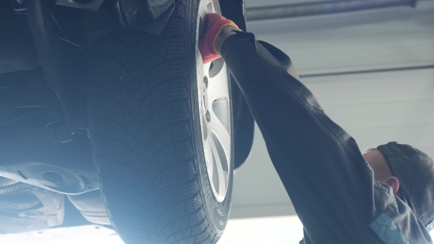 Car mechanic replacing car wheel brake shoes of lifted automobile at repair service station | Shutterstock HD Video #1041095266