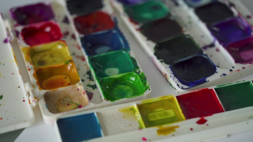 Brush takes different colors of watercolor paints from a palette and mixes them | Shutterstock HD Video #1041100165