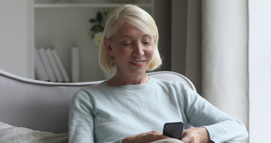Smiling middle aged older woman enjoying using smartphone sit on couch at home, happy mature adult lady holding handy device texting messages, playing games in mobile app looking at phone screen Royalty-Free Stock Footage #1041108271